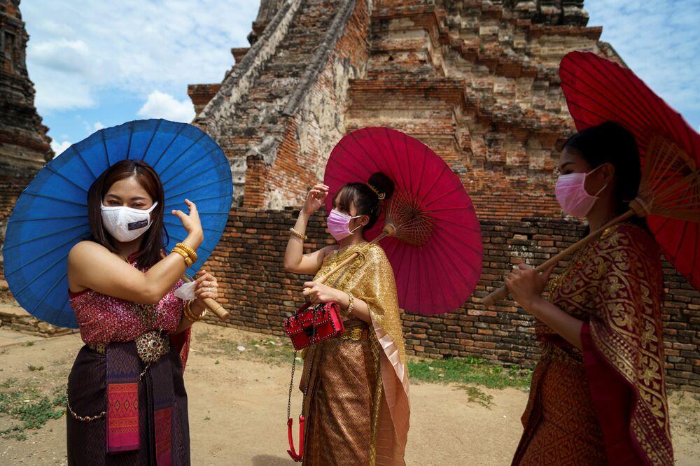 Mulheres com máscaras protetoras e trajes tradicionais na histórica cidade de Ayutthaya, Tailândia