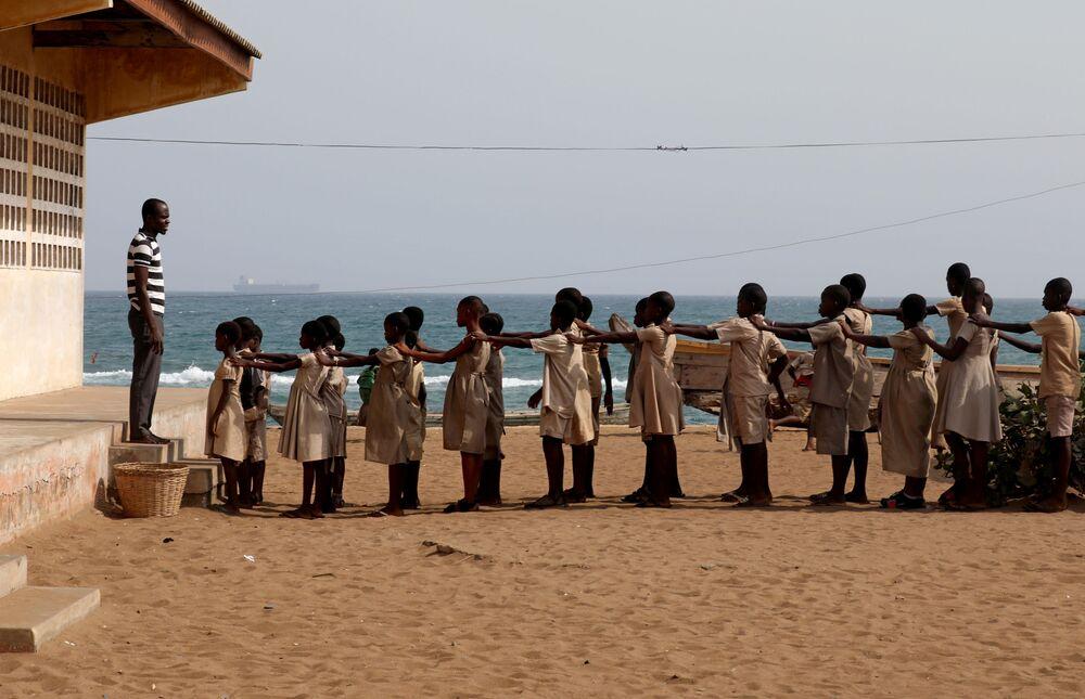 Alunos ficam em fila no pátio da escola, danificada pelas tempestades e erosão costeira, em Bagid, Togo