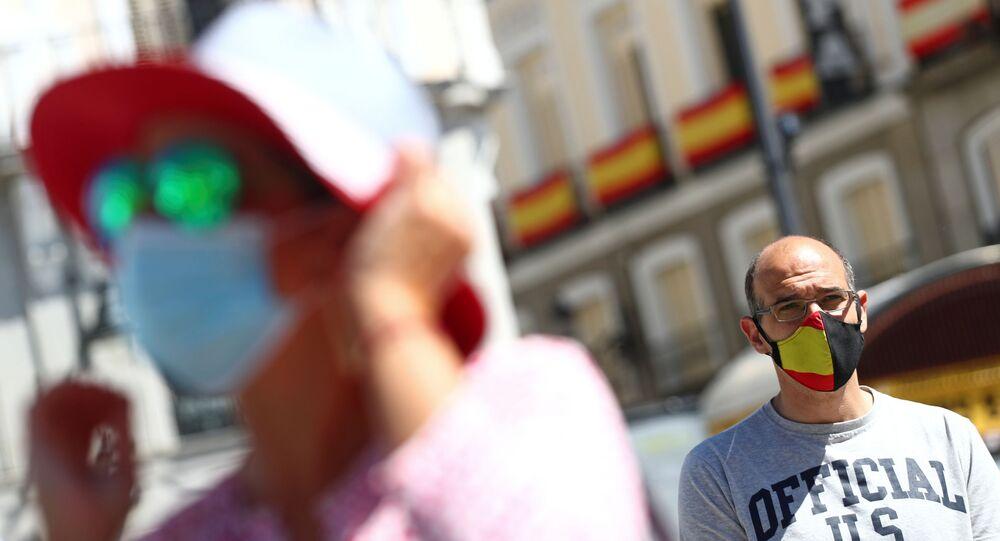 Homem usando máscara facial protetora com bandeira espanhola olha enquanto as pessoas se juntam para fazer um minuto de silêncio durante o último dos dez dias de luto oficial em memória dos que morreram da doença do coronavírus (COVID-19), praça Puerta del Sol, em Madri, Espanha, 5 de junho de 2020