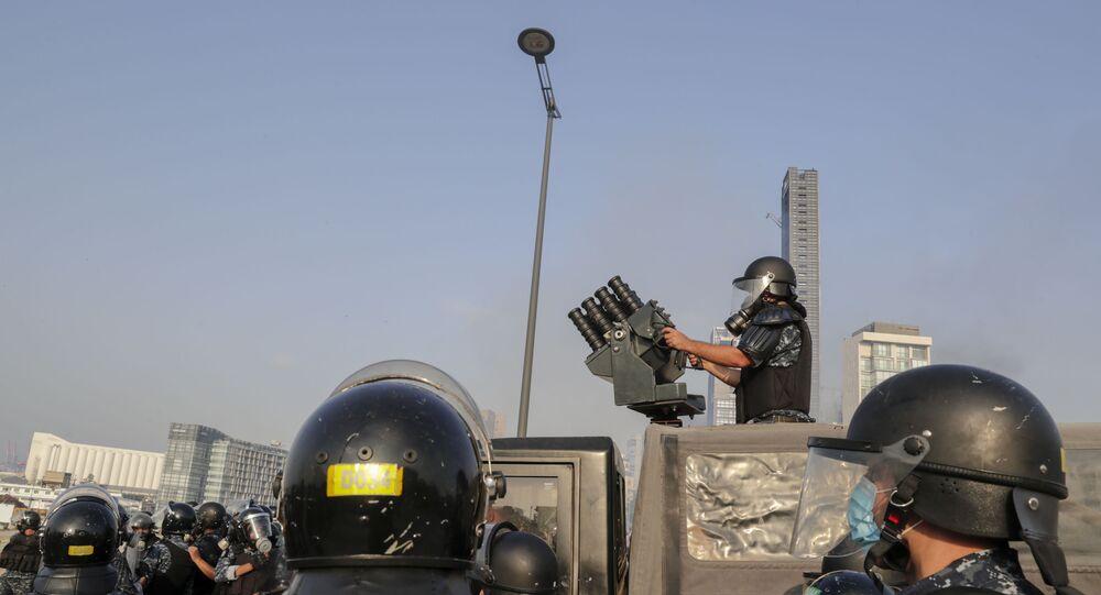 Policial se prepara para disparar bomba de gás lacrimogêneo contra manifestantes em Beirute, Líbano, em 6 de junho de 2020