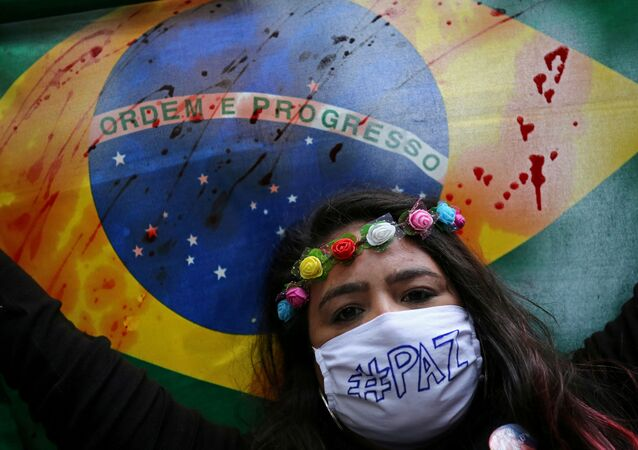 Manifestante carrega bandeira do Brasil manchada, durante protesto contra o governo Bolsonaro, em Porto Alegre, 7 de junho de 2020