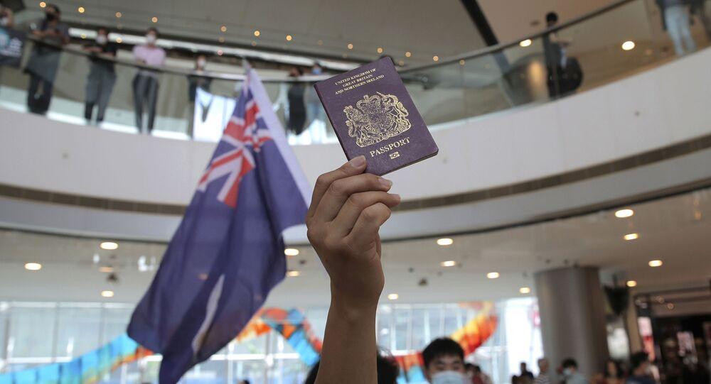Manifestante empunha bandeira do Reino Unido e passaporte britânico em centro comercial de Hong Kong, na China, 29 de maio de 2020