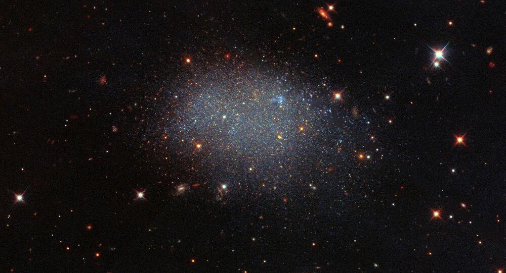 Diferentemente de uma galáxia espiral ou elíptica, a galáxia KK 246 parece brilho derramado sobre uma folha de veludo preta. KK 246, também conhecida como ESO 461-036, é uma galáxia anã irregular que reside dentro do Vazio Local, uma vasta região de espaço vazio