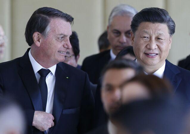 Em Brasília durante encontro dos BRICS, em 13 de novembro de 2019, o presidente brasileiro Jair Bolsonaro (à esquerda) caminha ao lado do presidente chinês Xi Jinping (à direita).