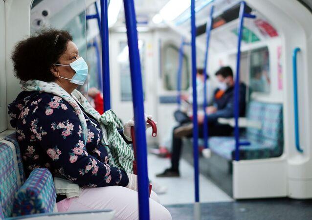 Mulher usando uma máscara facial em um trem do metrô de Londres, durante a pandemia de COVID-19, Londres, Reino Unido, 10 de junho de 2020