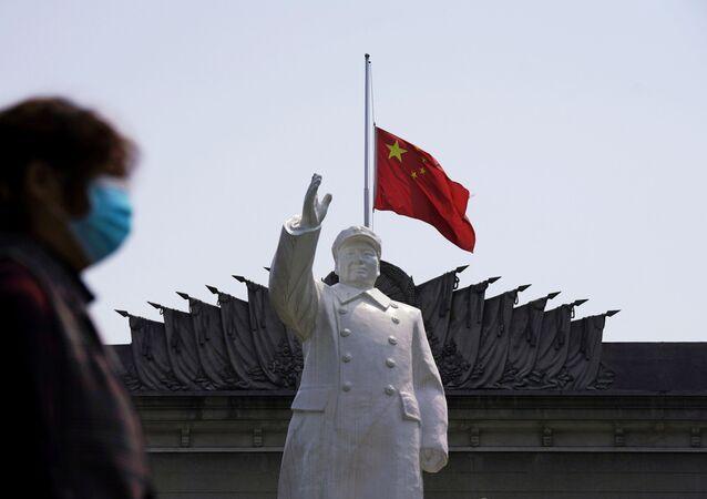 Estátua do líder chinês Mao Tsé-Tung exposta diante de uma bandeira da China em Wuhan, na província de Hubei