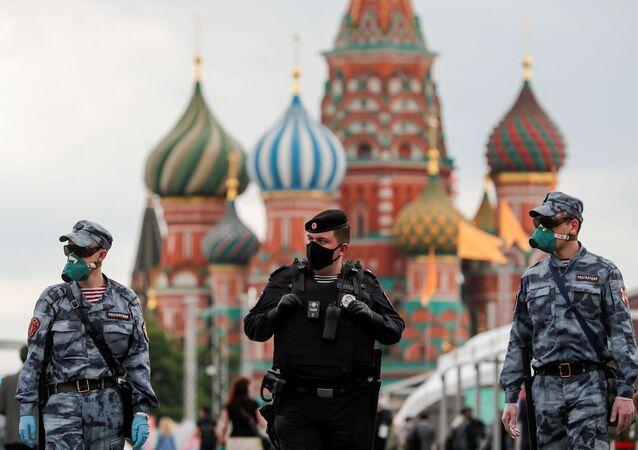 Oficiais de segurança russos usam máscaras na feira anual na Praça Vermelha, em Moscou