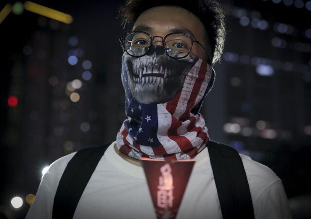 Jovem usa máscara com bandeira dos EUA durante vigília para marcar o massacre da Praça Tiananmen de 1989, em Hong Kong, 4 de junho