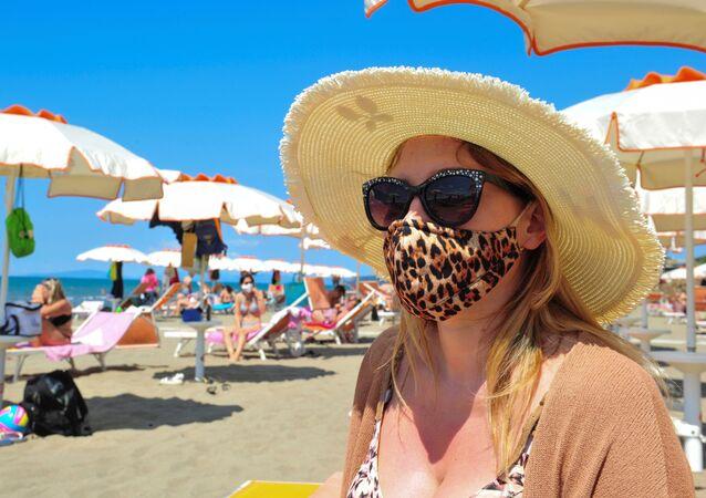 Mulheres usando máscaras se bronzeiam na praia espanhola de Malvarrosa, em Valência