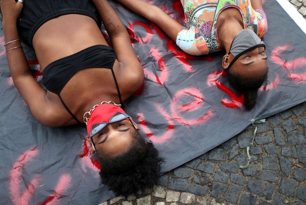 Meninas deitam em uma calçada de Copacabana com máscaras de proteção em meio a protestos pela democracia