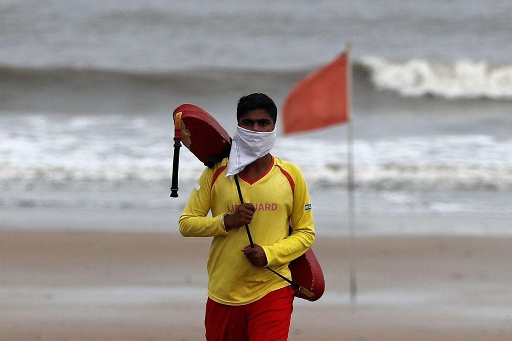 Salva-vidas caminha com máscara improvisada em praia na Índia antes da chegada do ciclone Nisarga