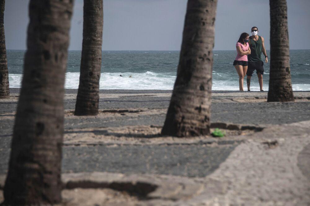 Casal com máscaras caminha pela praia do Arpoador no Rio de Janeiro