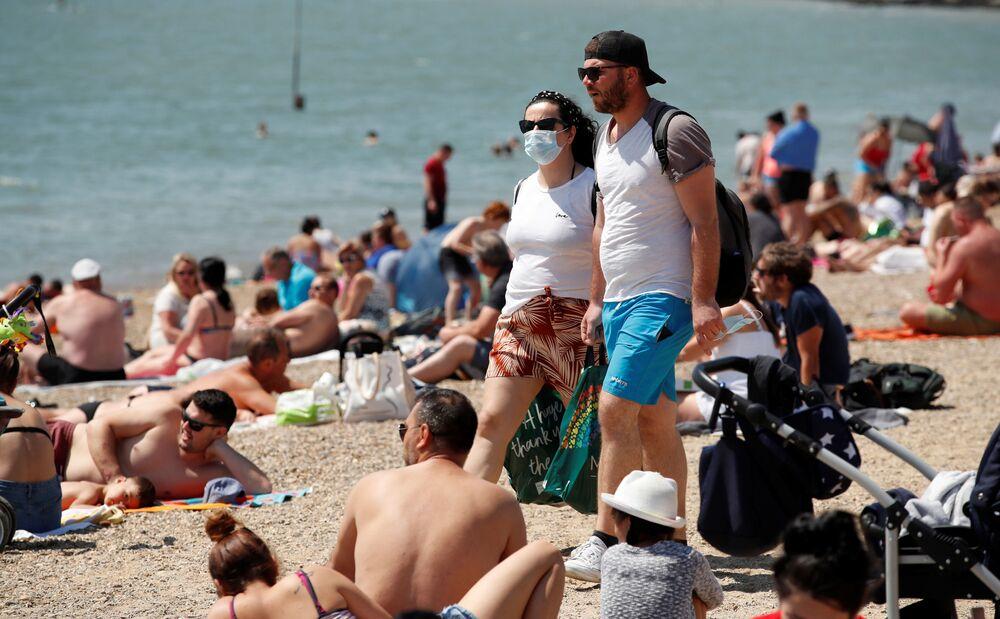 Mulher com máscara para se proteger do coronavírus em praia do Reino Unido