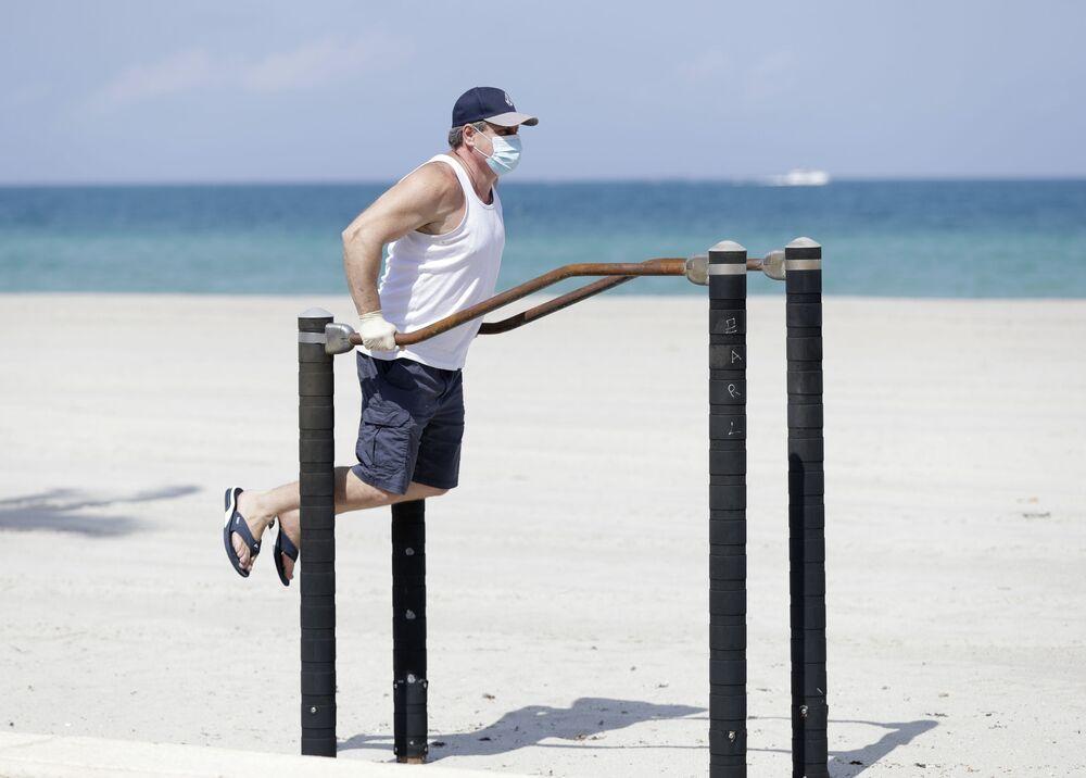Homem se exercita com máscara de proteção do coronavírus em praia da Flórida, nos EUA