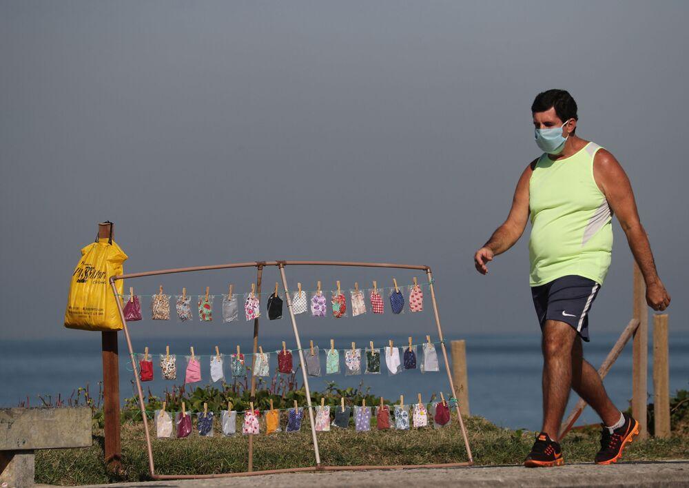 Homem caminha em frente a ponto de venda de máscaras de proteção do coronavírus em praia da Barra da Tijuca, no Rio de Janeiro