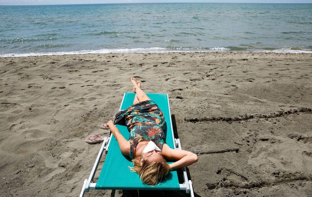 Mulher com máscara se bronzeia em praia próxima à capital italiana de Roma