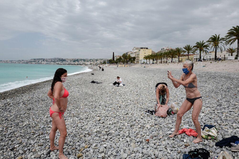 Mulheres com máscara aproveitam dia de sol em praia de Nice, na França