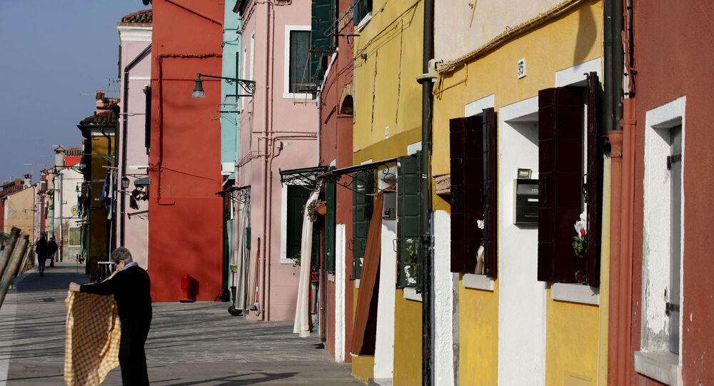 Idosa sacode toalha de mesa do lado de fora de sua casa na ilha de Burano, na Itália (imagem de arquivo)