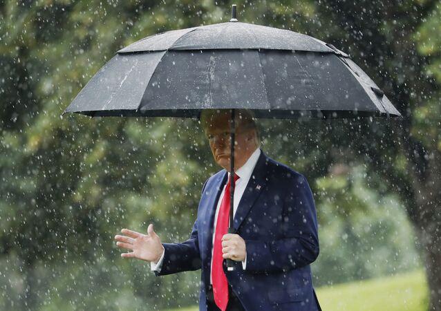 Presidente dos EUA, Donald Trump, se protege da chuva na Casa Branca, em Washington, 11 de junho de 2020