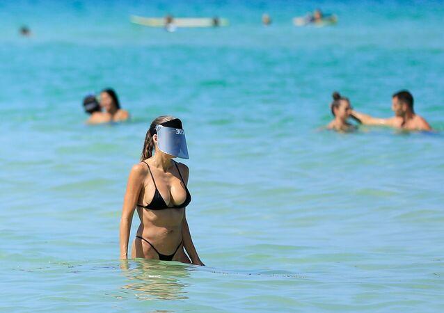 Mulher se banha com escudo facial em praia da Flórida