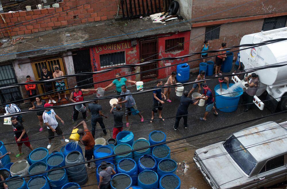 Moradores de Caracas, Venezuela, se organizam para receber água, enquanto alguns bairros da cidade vivem problemas com o fornecimento do bem