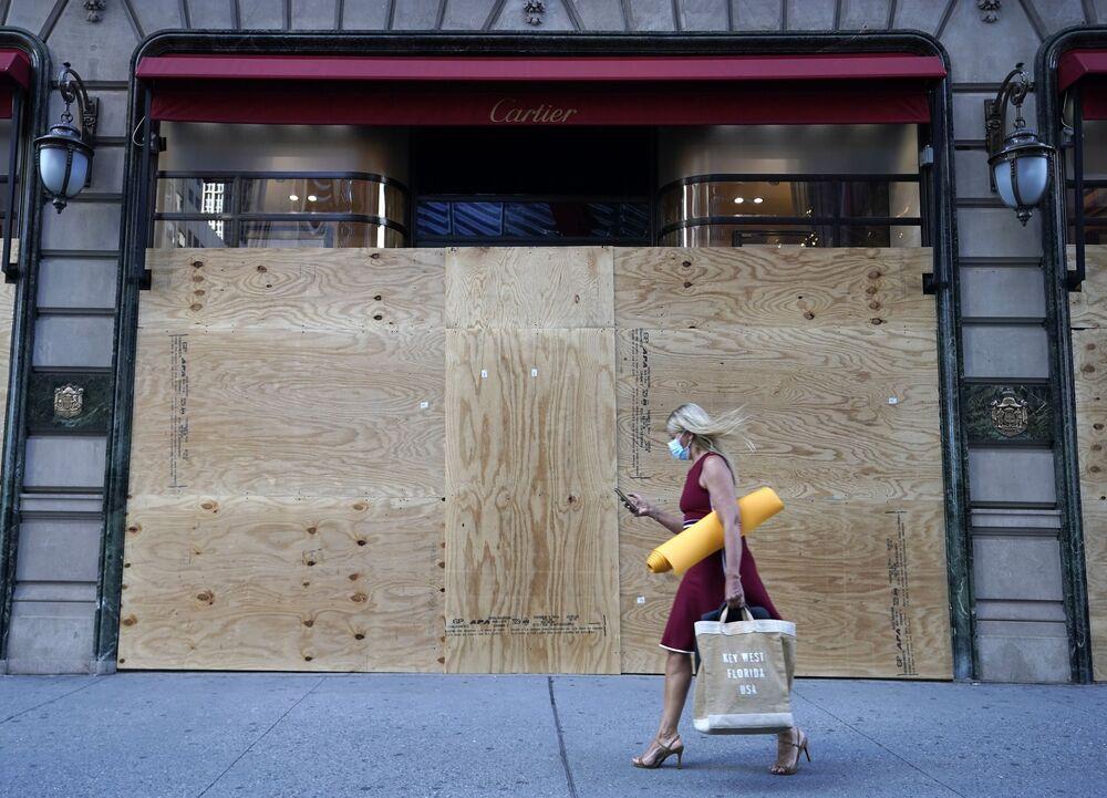 Mulher passa em frente de loja de joias e relógios Cartier, fechada com estrutura especial em Nova York, enquanto cidade recomeça a retomar atividades comerciais no contexto da pandemia