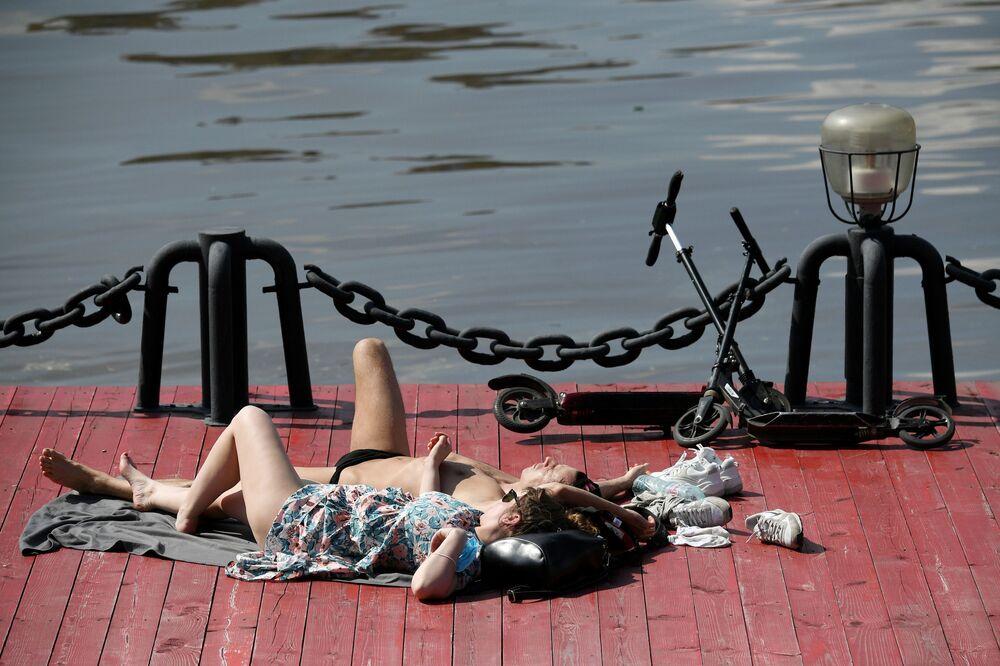 Casal toma banho de sol no Parque Gorky no centro de Moscou durante o verão na capital russa
