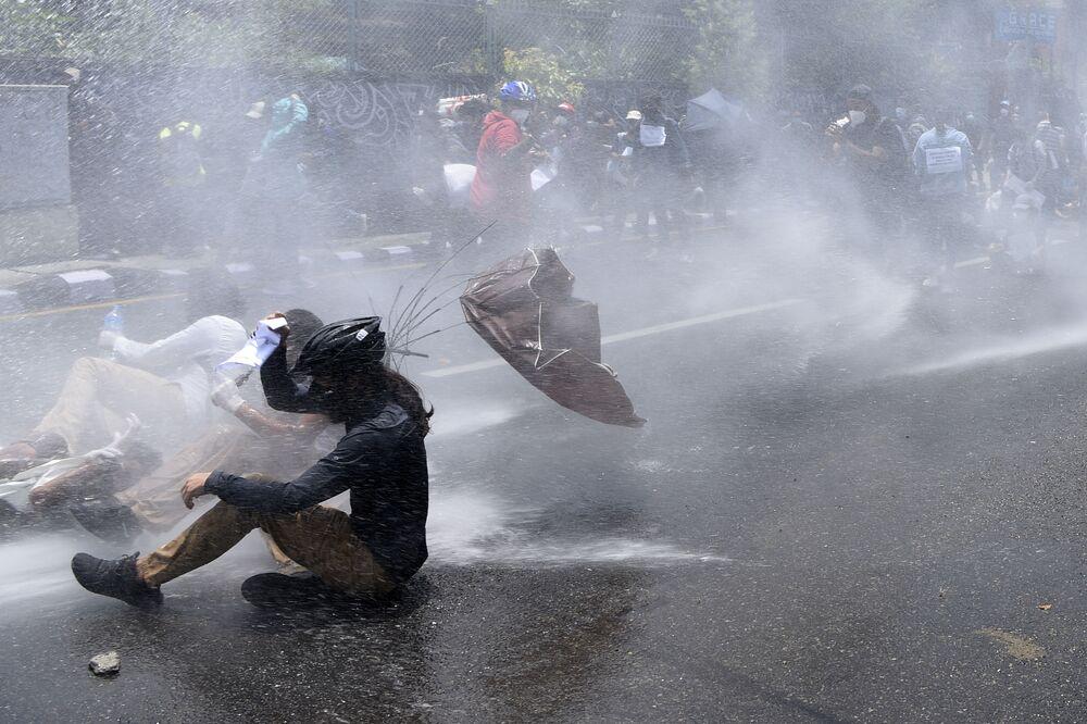 Polícia usa jato d'água para dispersar manifestantes insatisfeitos com a forma como o governo luta contra a pandemia do coronavírus em Catmandu, Nepal
