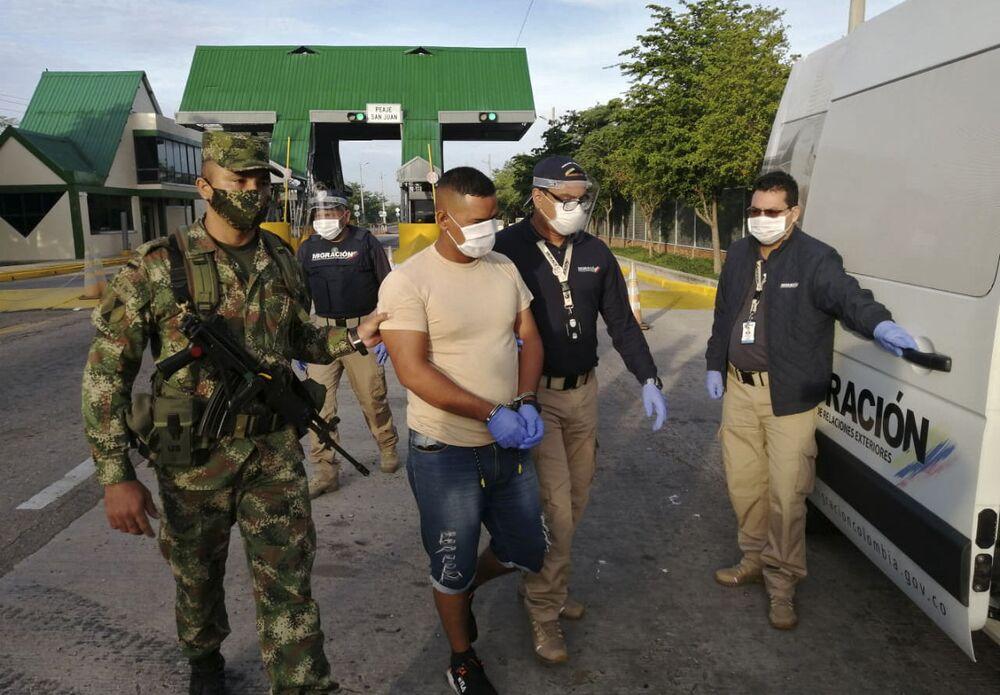 Agentes da Migração Colômbia conduzindo o alegado militar venezuelano Gerardo José Rojas Castillo durante sua expulsão do país após suspeita de espionar para a Venezuela