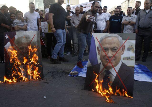 Palestinos queimam fotos de Donald Trump e Benjamin Netanyahu em Nablus, na Cisjordânia