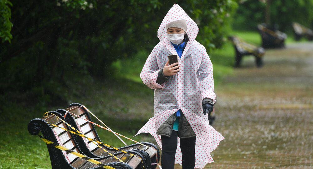 Menina, envergando máscara e e capa de chuva, passeando pelo Parque Kolomenskoye, em Moscou, Rússia