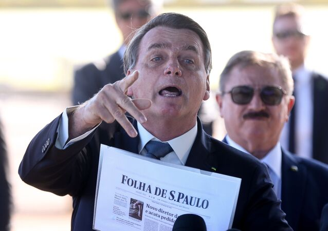 Presidente Jair Bolsonaro fala com a imprensa ao sair do Palácio da Alvorada, em Brasília, segurando um exemplar da Folha de S.Paulo