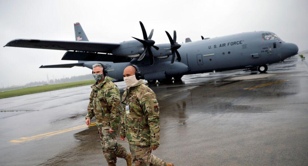 Soldados norte-americanos usando máscaras em frente a aviões de transporte C-130 durante um exercício militar em meio à pandemia, na Base Aérea de Yokota dos EUA, Japão, 21 de maio de 2020