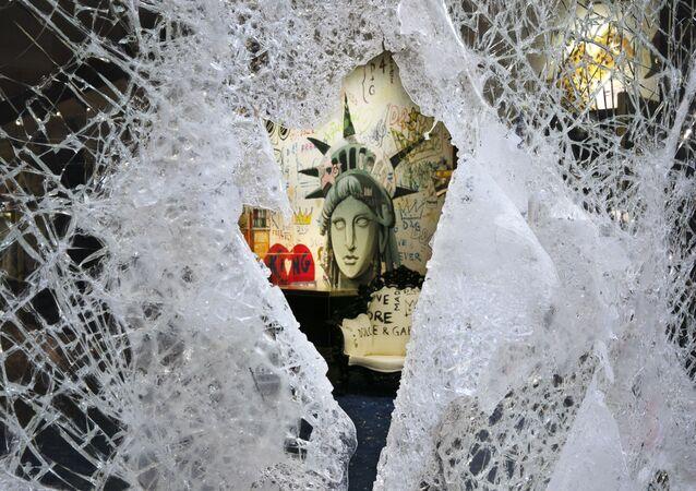 Pintura da Estátua da Liberdade é vista através de uma vitrine destruída da loja Dolce & Gabbana, 1º de junho de 2020, bairro do SoHo, Nova York