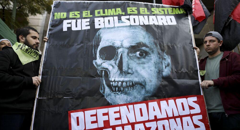 Cartaz diz Não foi o clima, é o sistema, foi Bolsonaro. Defenda a Amazônia é exibido durante protesto em Buenos Aires