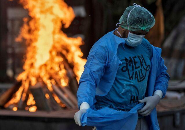 Motorista de ambulância na Índia troca seu equipamento de proteção pessoal, após paciente que ele transportava falecer de COVID-19, em Nova Deli, na Índia, 16 de junho de 2020