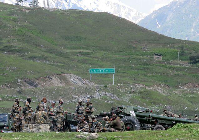Soldados indianos descansam próximos a armamentos de artilharia em um acampamento durante percurso em direção a Ladakh, na região fronteiriça com a China.