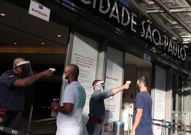 Seguranças checam a temperatura de clientes antes de entrar em shopping na cidade de São Paulo.
