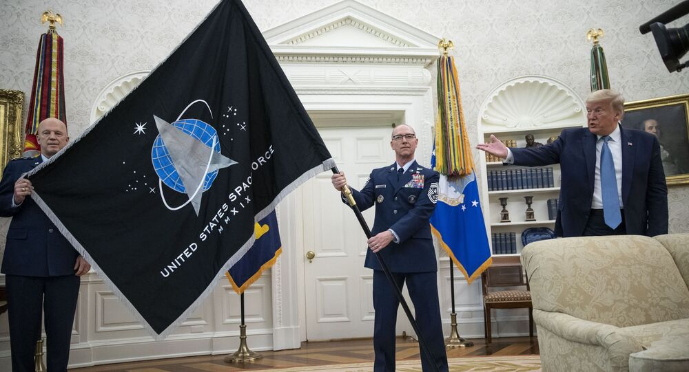 O general John Raymond, chefe do Comando Espacial dos EUA, à esquerda, e o sargento Roger Towberman, à direita, durante a apresentação, na presença de Donald Trump, da bandeira da Força Espacial na Sala Oval da Casa Branca, em Washington, 15 de maio de 2020