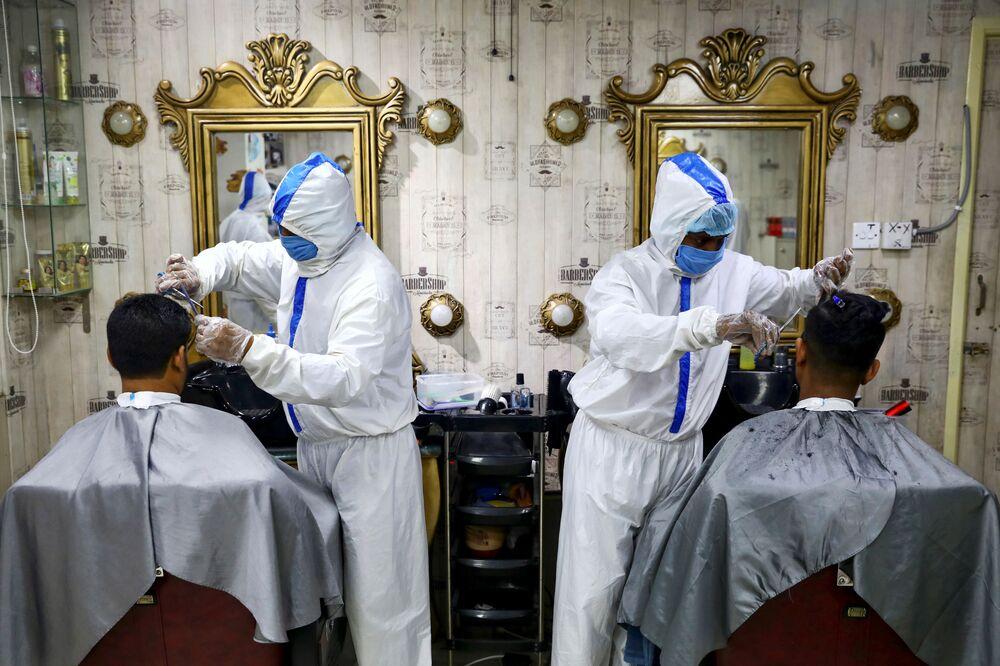 Barbeiros trabalhando com trajes sanitários durante a pandemia do coronavírus em Daca, Bangladesh