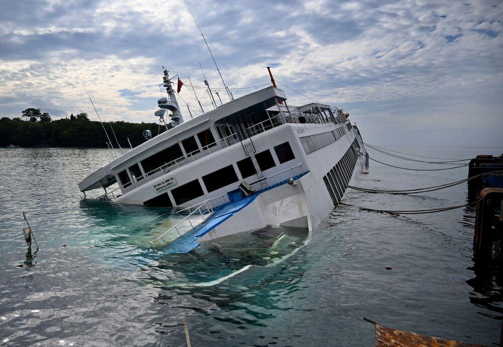 Balsa naufraga ao lado de píer em Karangasem, na ilha de Bali, ao tentar atracar
