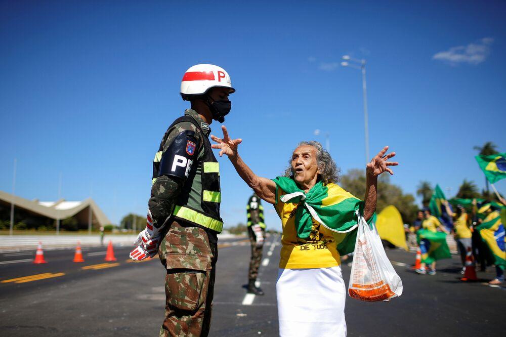 Idosa apoiadora do presidente Jair Bolsonaro participa de ato contra a Supremo Tribunal Federal falando com um soldado em frente ao quartel-general do Exército em Brasília