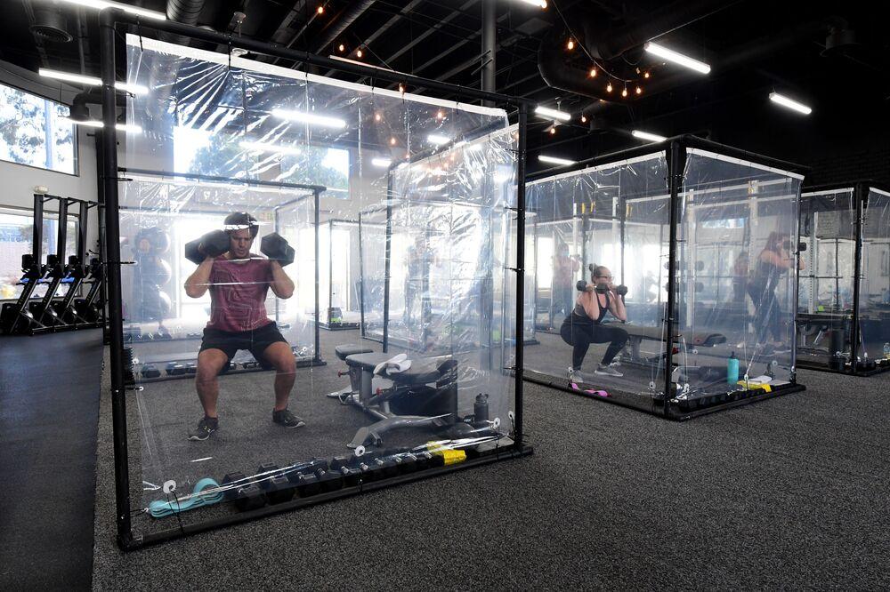 Frequentadores da academia Inspire South Bay Fitness fazem exercícios em boxes especiais obedecendo as regras do distanciamento social na Califórnia