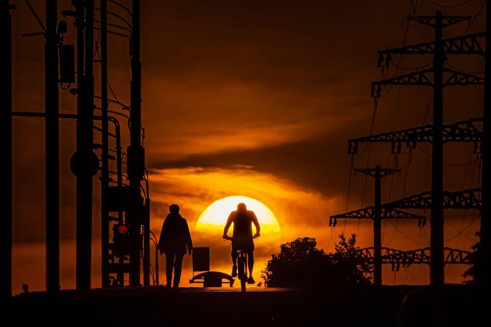 Homem anda de bicicleta tendo como fundo o pôr do sol em Moscou