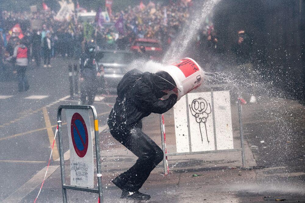 Manifestante coloca balde em sua cabeça para se proteger de canhão d'água durante protesto de agentes da saúde na cidade francesa de Nantes