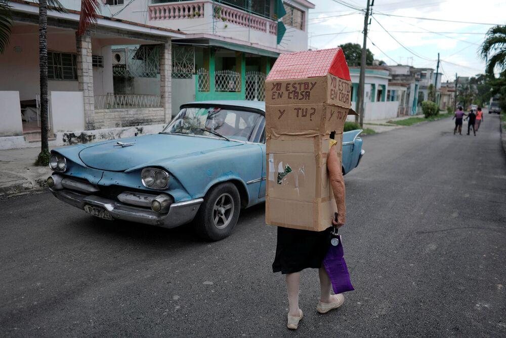 Enfermeira aposentada Feridia Rojas, 82, caminha ao lado de carro antigo em rua de Havana
