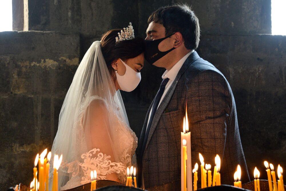 Casal se beija durante sua cerimônia de casamento usando máscaras no vilarejo de Saghmosavan, na Armênia