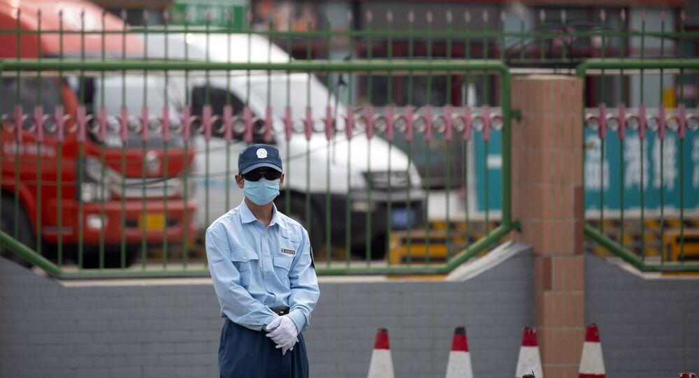 Segurança monta guarda em frente do mercado de Xinfadi em Pequim, sábado, 13 de junho de 2020. Pequim fechou o maior mercado da cidade após a descoberta de 7 casos do novo coronavírus nos dois dias anteriores