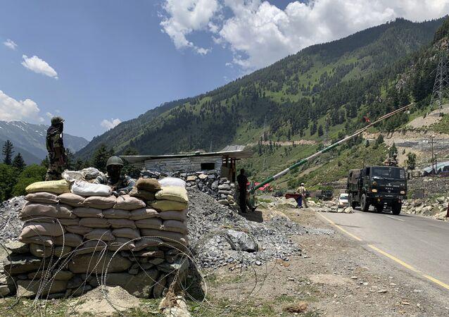 Soldados paramilitares indianos montam guarda enquanto um comboio do Exército indiano se desloca na rodovia Srinagar-Ladakh em Gagangeer, nordeste de Srinagar, Índia, 18 de junho de 2020