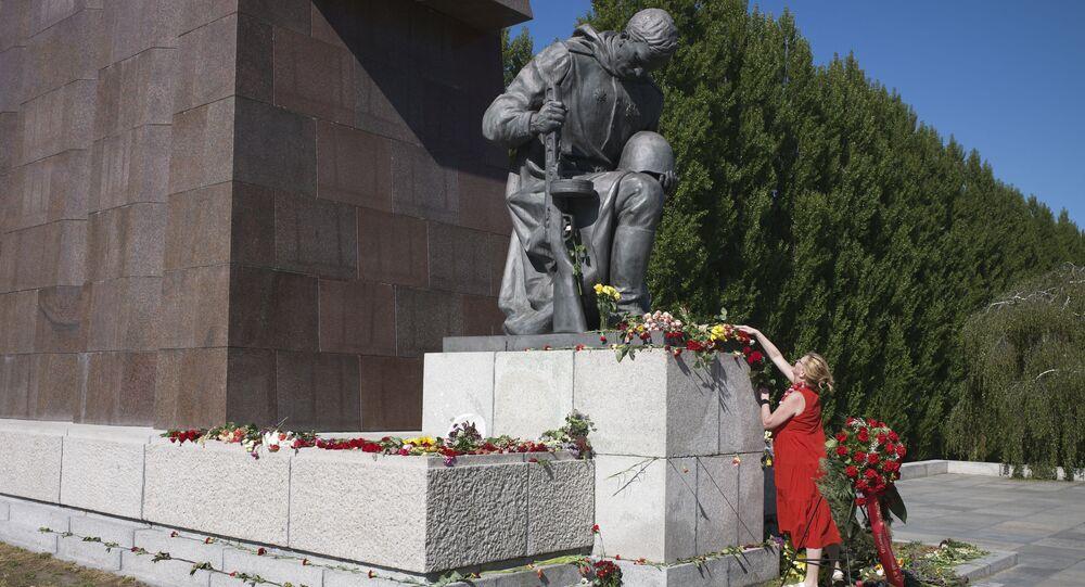 Mulher colocando flores no monumento ao soldado do Exército Vermelho na cerimônia de comemoração dos 75 anos do Dia da Vitória, distrito de Treptow, Berlim, Alemanha, 9 de maio de 2020
